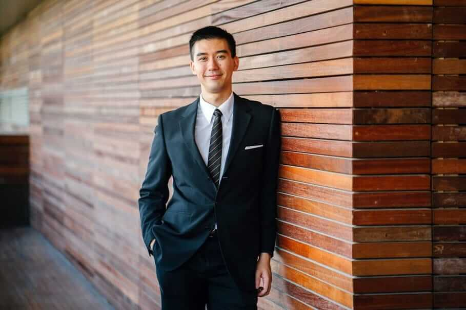 Male lettings mediator in business suit standing next to a wooden wall