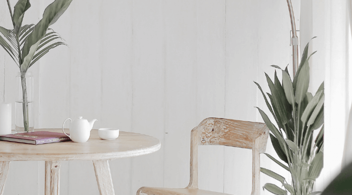 Wooden table and chair with plants in front of white wall