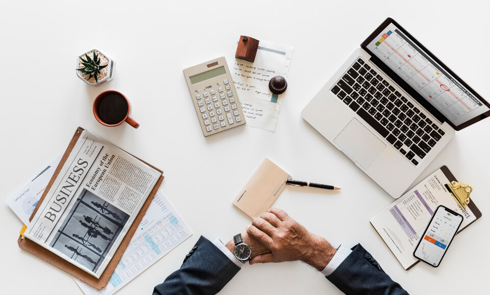 Flatlay with laptop, newspaper, calculator and businessman's arms
