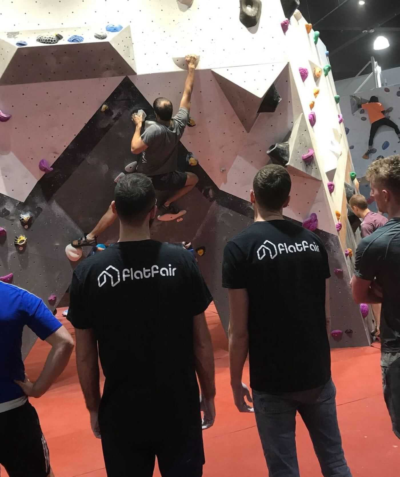Male colleagues rock climbing with flatfair tshirts