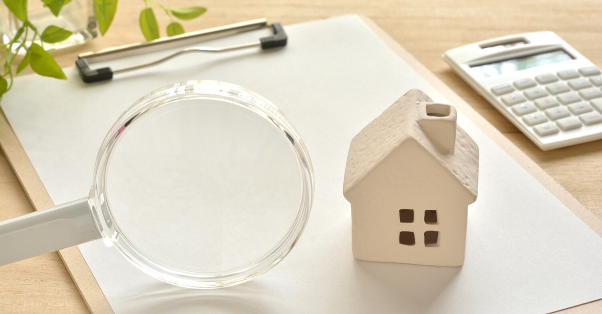 Clipboard with magnifying glass and miniature house to demonstrate property lettings glossary