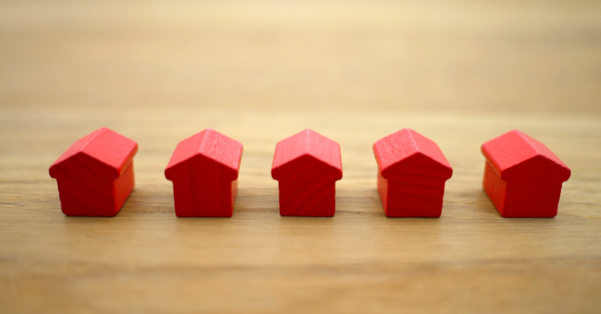 Five red wooden houses on a wooden desk.